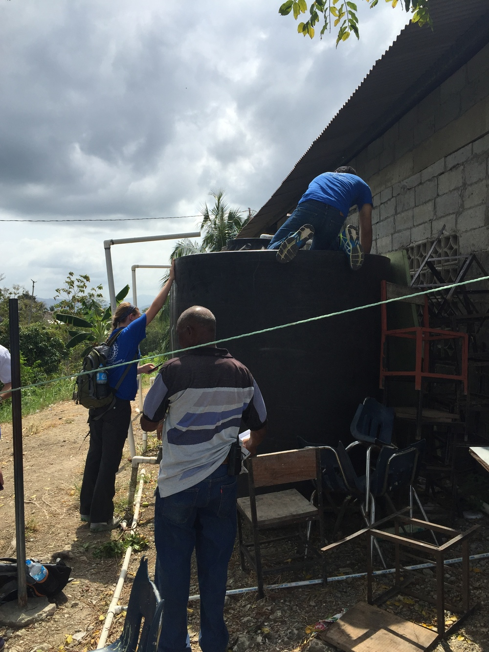 """The """"Engineering Team"""" taking measurements of their water tanks which no longer function."""