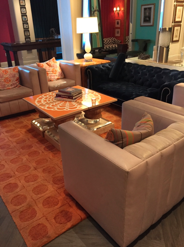 This orange area rug contrasts well with the dark blue sofa and brings out the orange accents in the accent pillows.