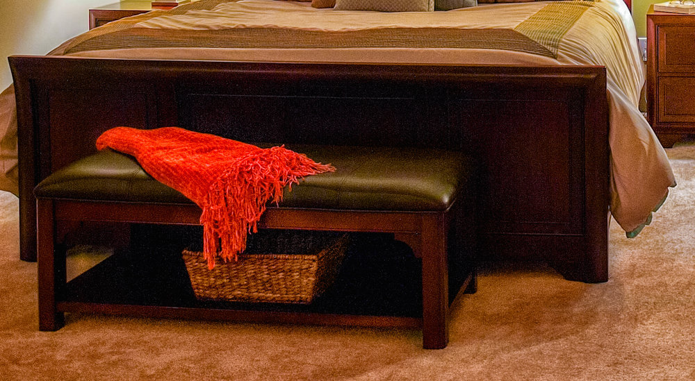 for this bedroom suite I draped an orange throw on the brown leather bench for color and texture.