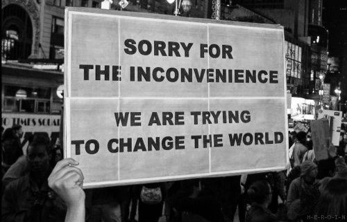 "Sign that says ""Sorry for the inconvenience we are trying to change the world."""
