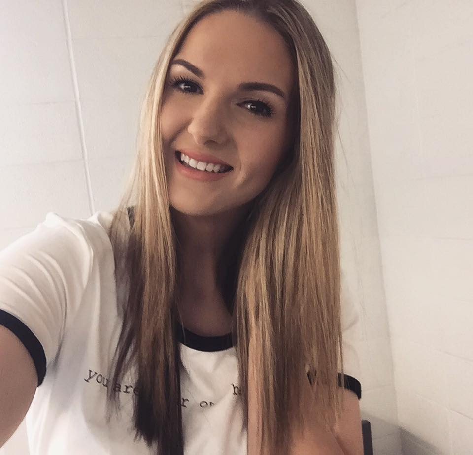 Image Description: A young woman (Carolanne) with long blonde hair, poses in a selfie against a white tiled wall. She is smiling and tilting her head to the right. She is wearing a white t-shirt with unclear lettering.