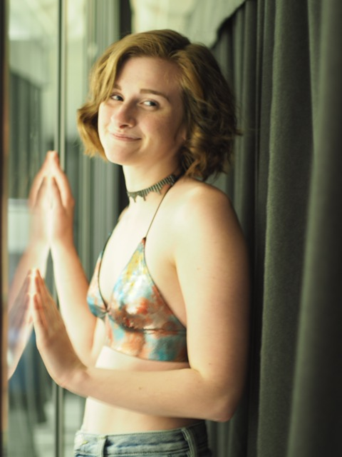 Image Description: A young woman, Eleanor, with short light brown hair, smiling over her shoulder, standing in front of a window.