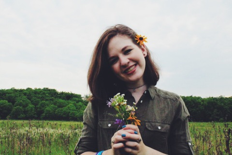 Image Description: A young woman, Katy, smiling with dark brown hair in a field holding a small bouquet of flowers.