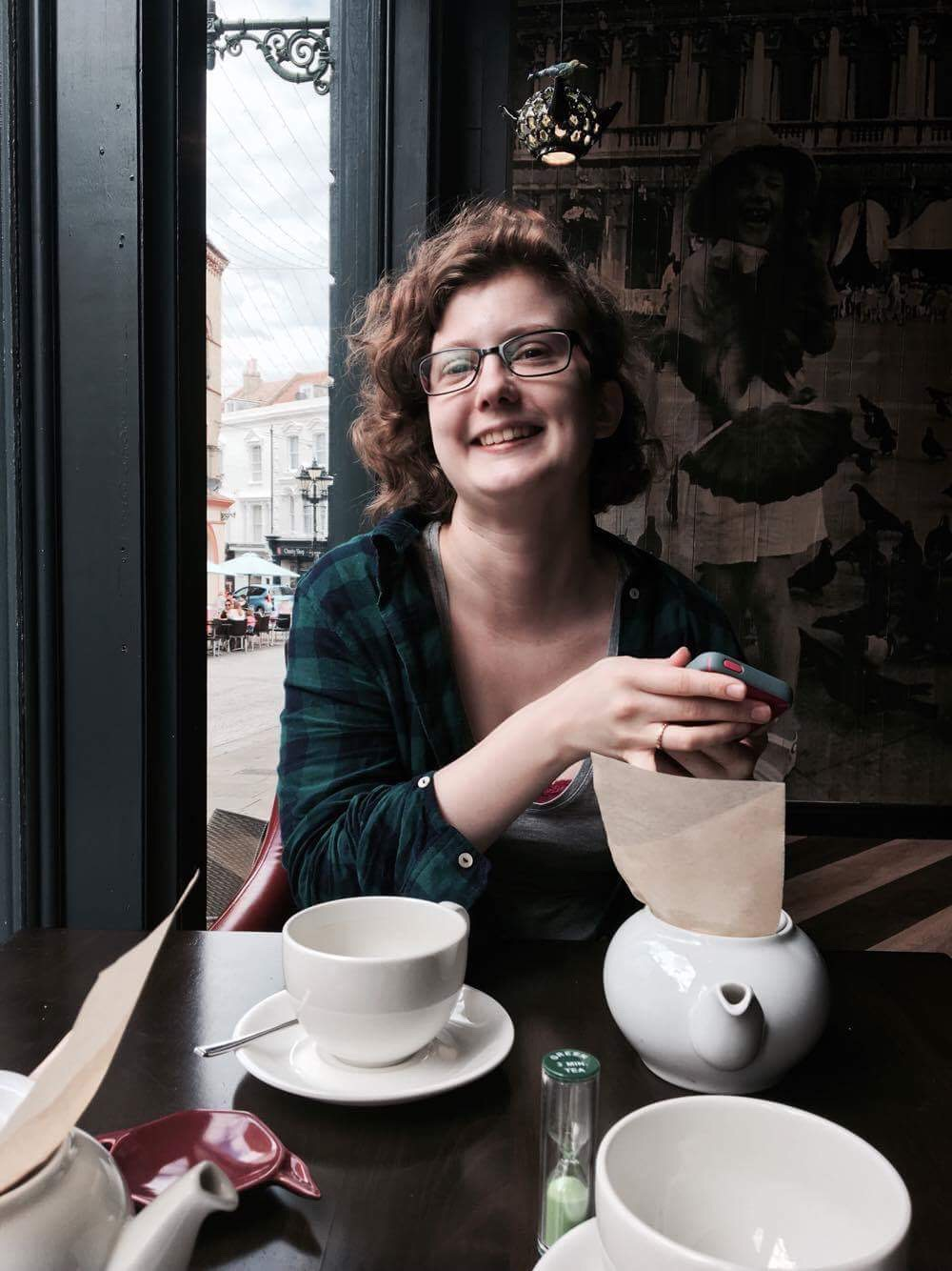 Image Description: A young woman with curly brown hair and glasses sits in a restaurant with teacups in front of her, smiling and holding her phone.