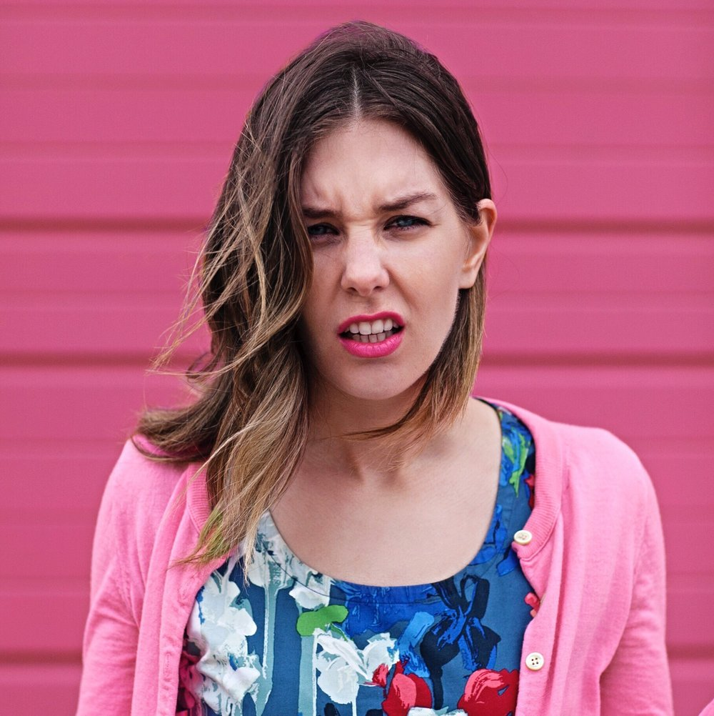 "Sarah posed in a colorful top with a pink sweater against a pink wall making a funny ""WTF?"" face."