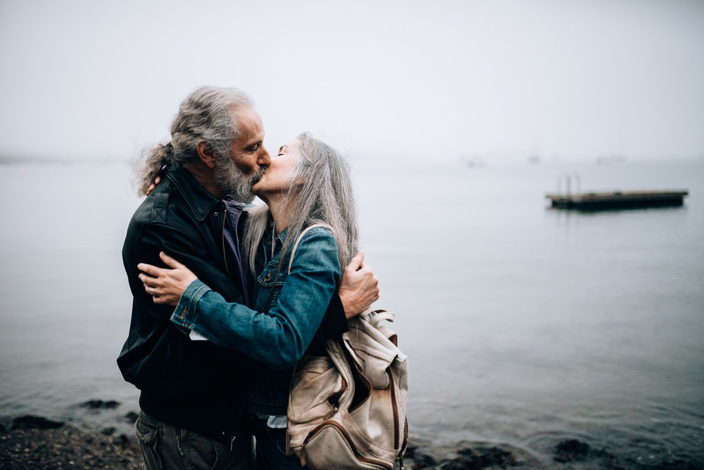 A middle aged couple with beautiful grey hair share a passionate kiss in front of the harbor in Camden, Maine.