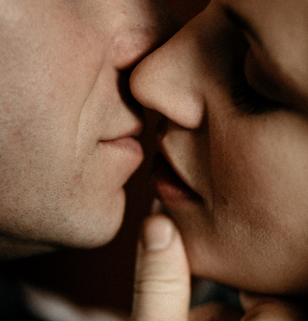 A close up and abstract photograph of two people kissing.