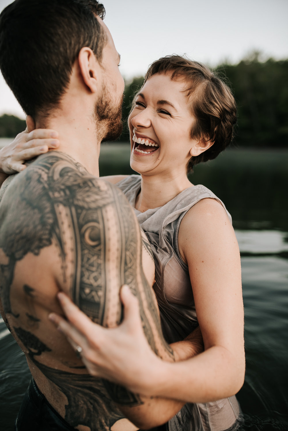 A young woman laughs while holding onto her tattooed husband while standing in water.