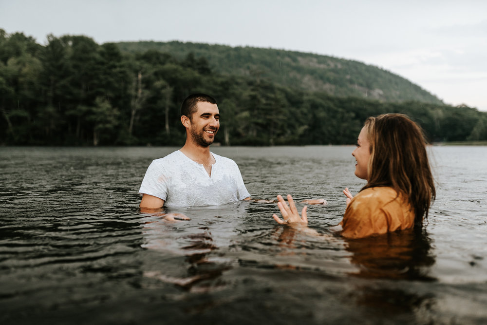 couple splashing in the water during their anniversary session at one of Camden Maine's best swim spots