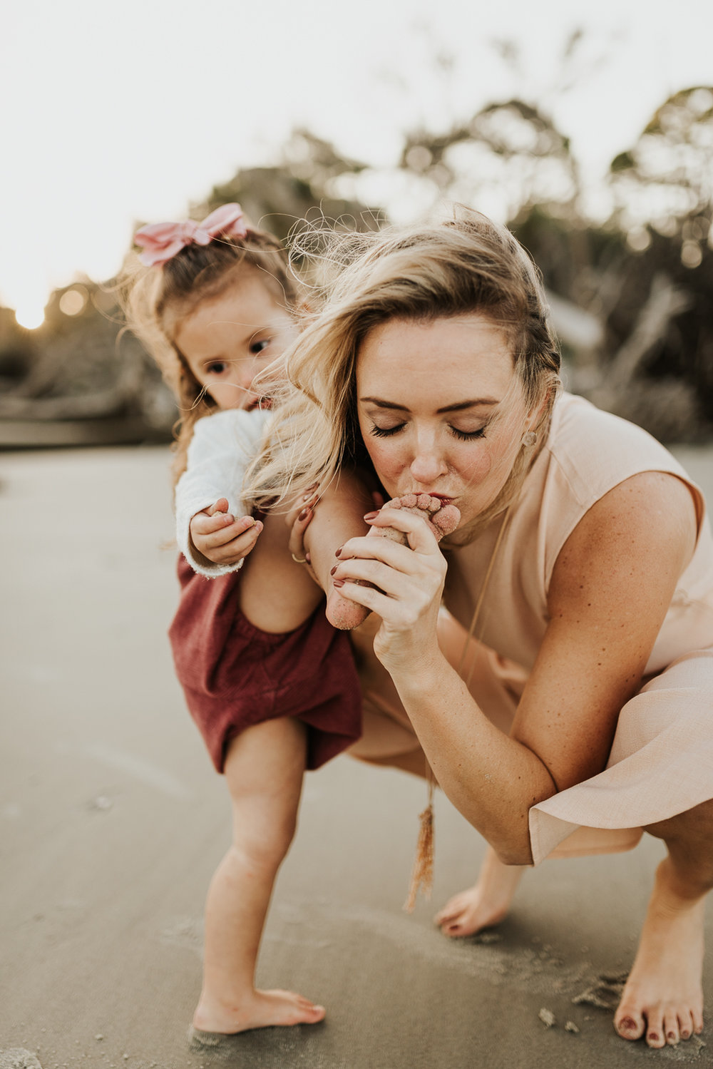 mother kissing her daughter's boo-boo during a family session in Beaufort SC