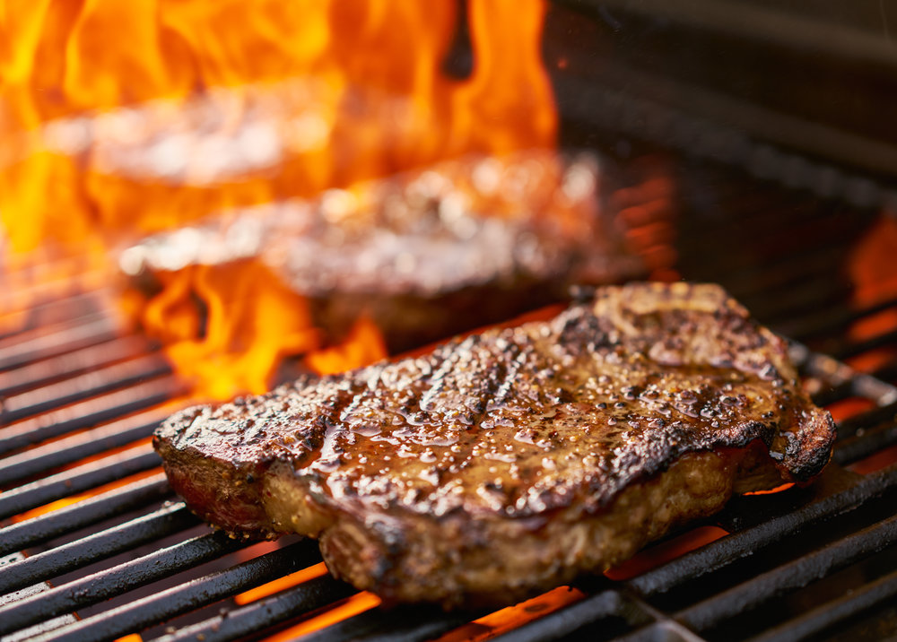 bigstock-grilling-new-york-strip-steaks-122926346.jpg