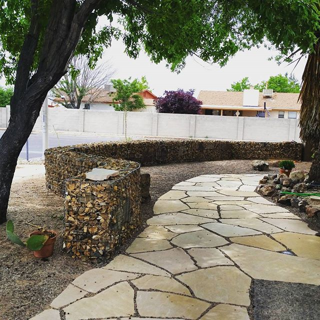 """One of our latest #hardscape designs. This #gabion wall is 3 feet by 70 feet long and 18"""" deep. They can be used as retaining walls or, like in this case, a decorative, free-standing privacy screen. Of course we created the #flagstone patio as well. #Native plantings will be coming soon to compliment and complete this project. #southwesthorticulture #xeriscaping #xeriscape #landscaping #landscape"""
