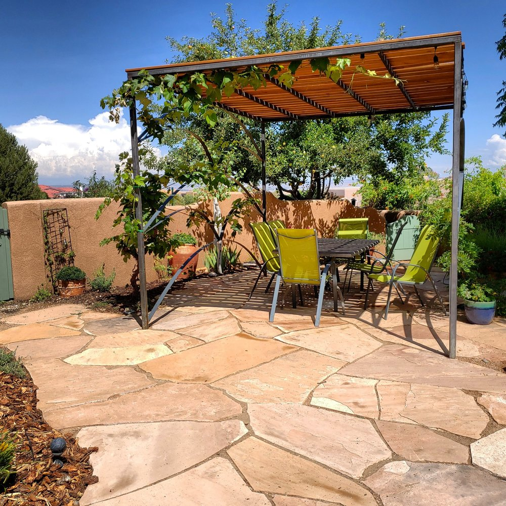 Here's another custom, welded steel #pergola built by Louis and his crew with a grape and a wisteria growing up the sides. We also built this #flagstone #patio for the client who had a poorly built, mismatched flagstone patio previously. We are very grateful to have such hard working, talented artisans on our team. Bob taught us this flagstone style years back and it really stands out from 99% of the flagstone work we see around town.  #southwesthorticulture #horticulture #landscapes #landscaping #landscapedesign #nativeplants #xeriscaping #xeriscape #waterconservation #gardening #albuquerque #newmexico