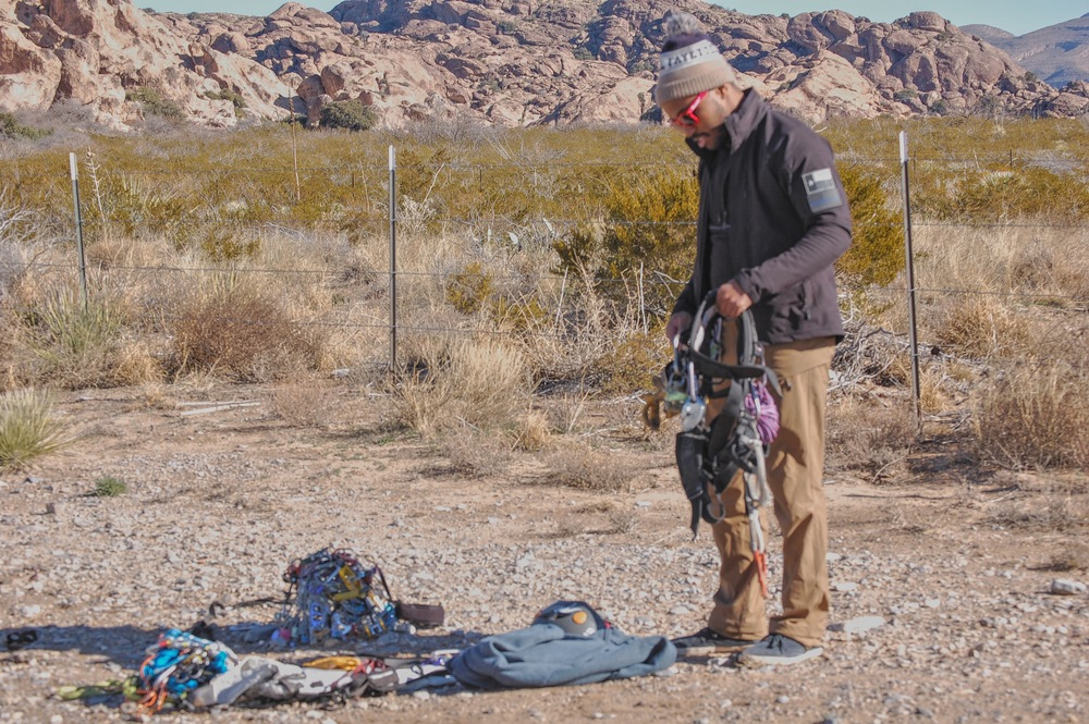 "Mario ""Racking Up"" for some Trad at Hueco Tanks. A small fraction of Mario's gear in a heap on the ground."
