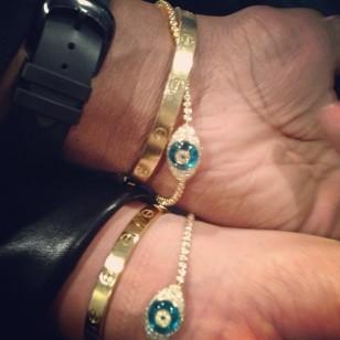 Kim Kardashian and Kanye West wearing matching Cartier Love Bracelets and Lorraine Schwartz Evil Eye Bracelets on Instagram.