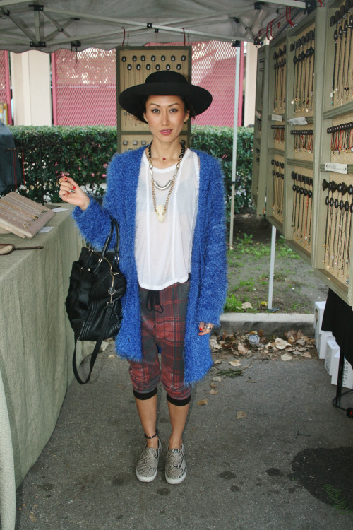 This fashion blogger did some jewelery shopping while she combined high fashion concepts and casual day wear in all the right ways!  Her textured bright blue cardigan, plaid joggers, and snake skin sneakers are topped off perfectly with a wide brim bowler hat.  This balance of casual with style keeps her ready for just about any occasion for the day.  –  Melrose Trading Post  Los Angeles, Ca  Neighborhood:  Melrose