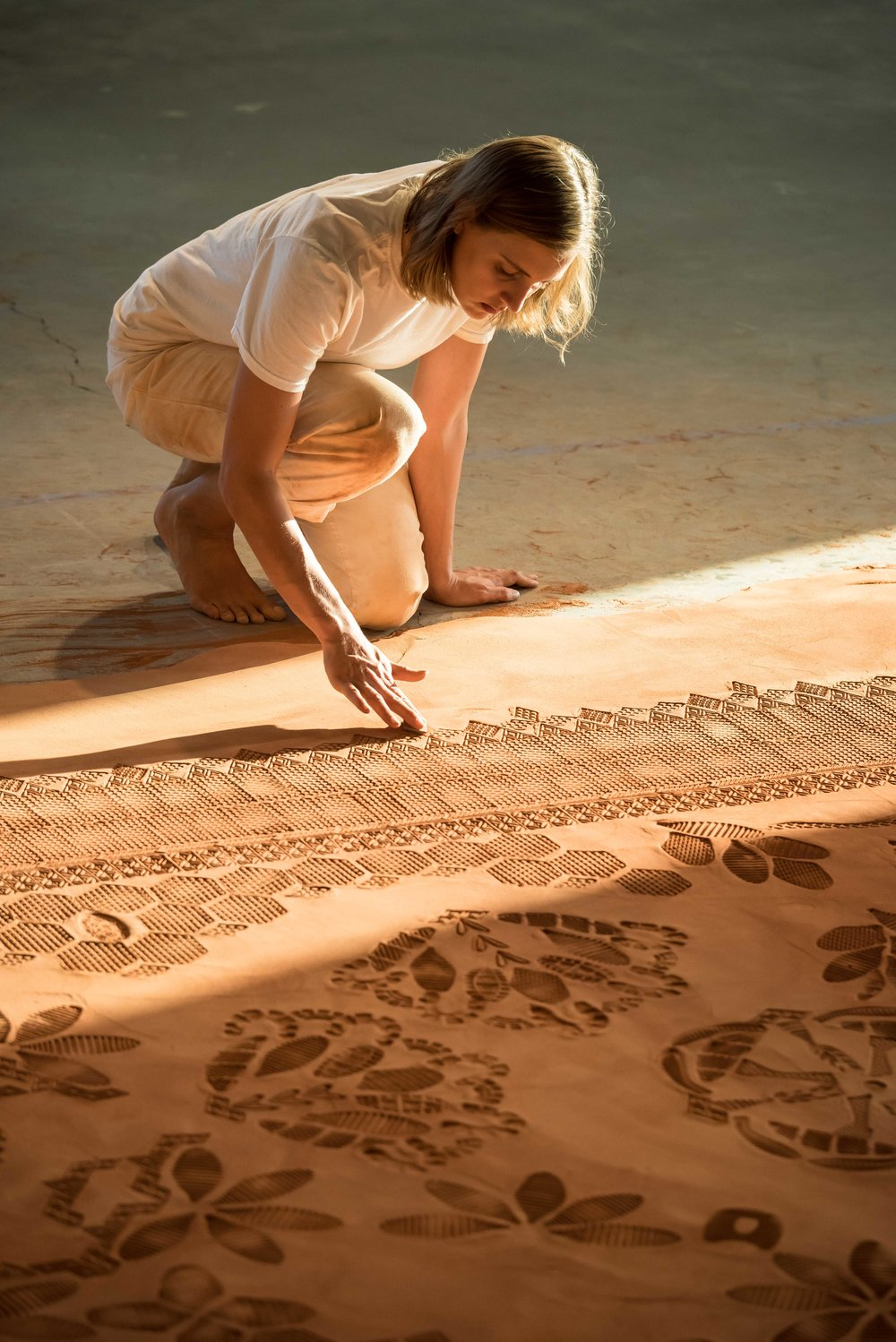 Rena Detrixhe presses designs into a Red Dirt Rug installation. Photo by: Mark Andrus