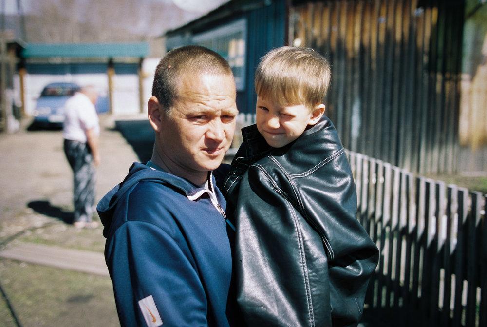 Nikolay is keeping his son warm under his jacket. Photo: Contax 645 + Kodak