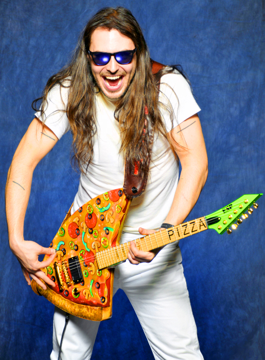 "Andrew W.K. had a guitar made in the shape of a pizza. No surprise. The dude likes to party and what's the one food most associated with parties? Pizza. It's the Alpha and Omega of parties.    Thanks to  Clif  for sending this my way. He suggested I invent a ""P"" chord to commemorate this achievement in pizza music. I'll see if I can work with Mr. W.K. on that. You can see more photos of  Andrew W.K. licking his new instrument on his site ."