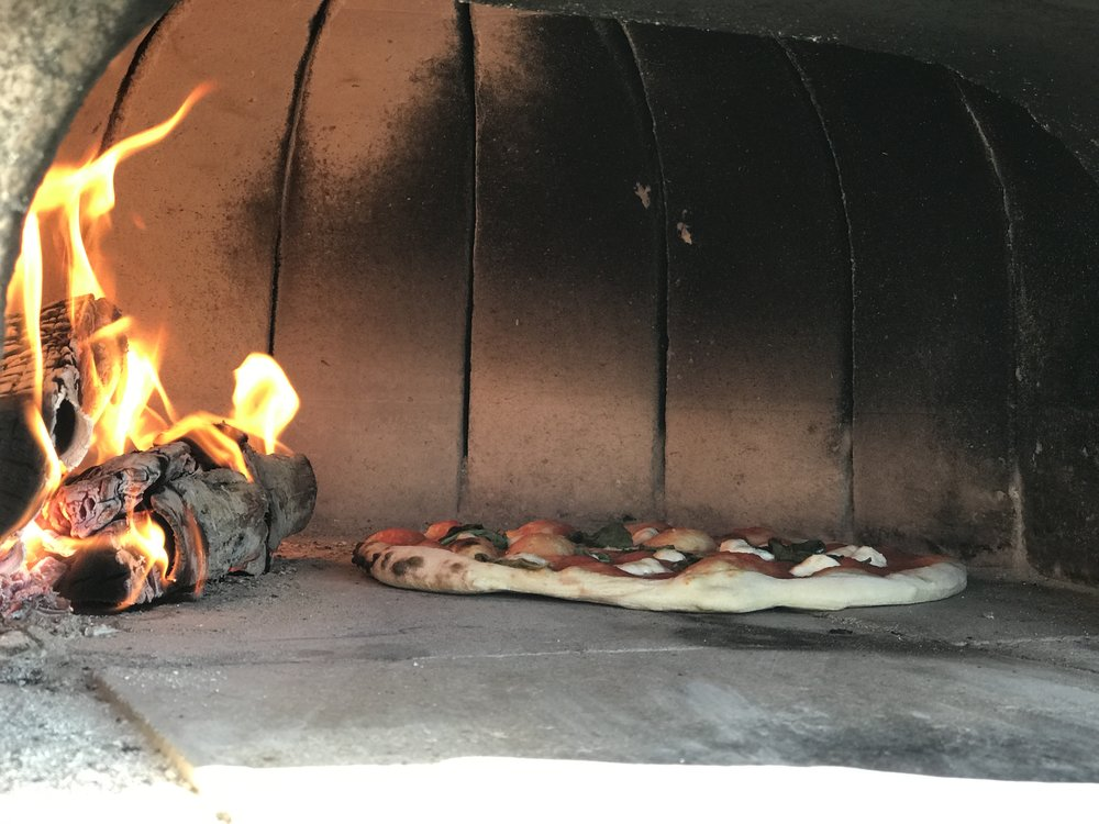 This is a pizza inside a brick oven getting all charred up.
