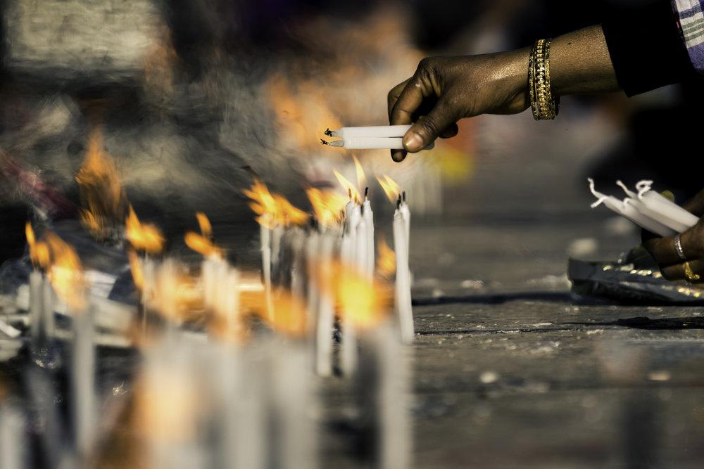 Pilgrims lighting candles to begin their prayers.