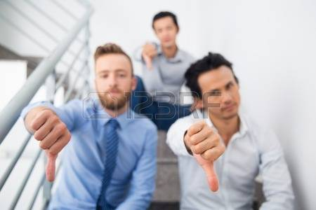 66456413-group-of-multiethnic-businessmen-showing-thumb-down-serious-managers-sitting-on-stairs-and-looking-a.jpg