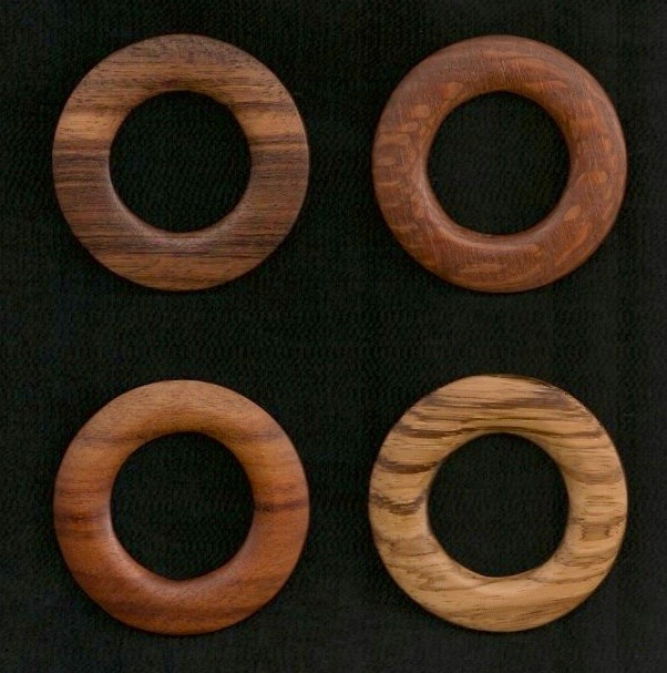 4 wooden rakusu rings against a black background.