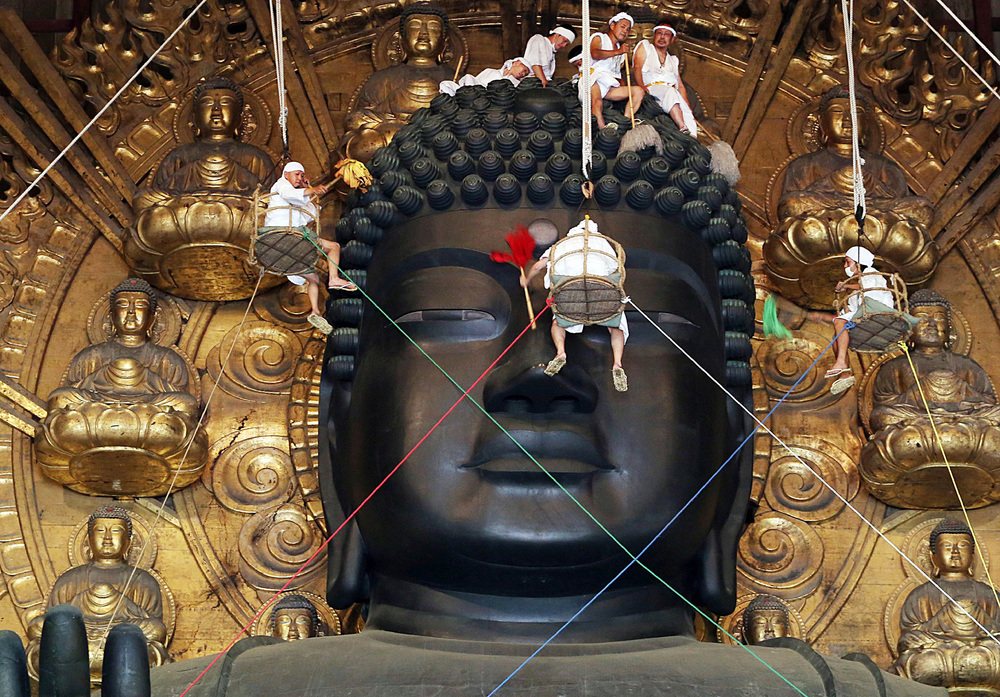 Something went wrong, don't worry the monks are busy fixing it. [Image Description: Monks hang from ropes and baskets cleaning a giant statue.]