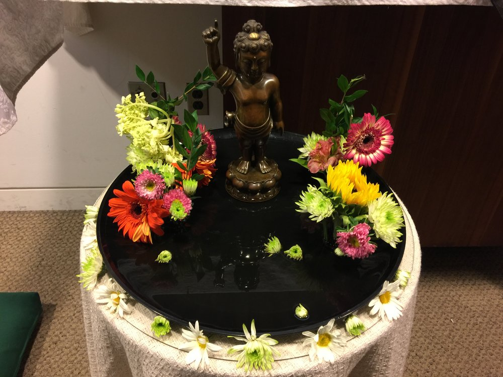 The  hana mido , flower altar, with a statue of Baby Buddha surrounded by spring flowers.