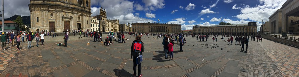 A panoramic shot of NBZ member Heidi, wearing a red backpack, standing in the middle of the Plaza de Bolívar in Bogotá, Columbia.