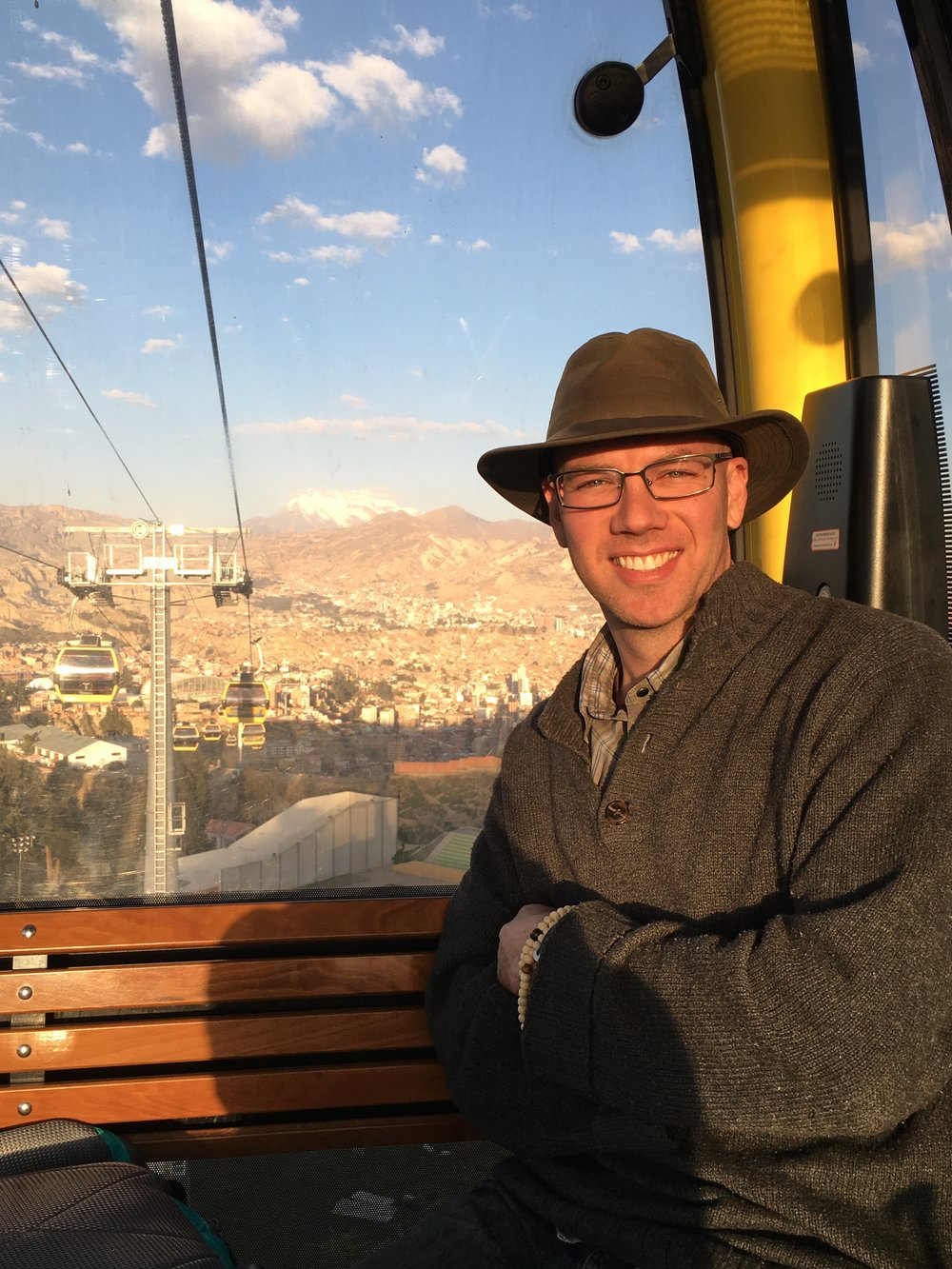 Ōshin smiling wearing a wide brim hat and sweater, riding the teleferico with Mount Illimani behind him.