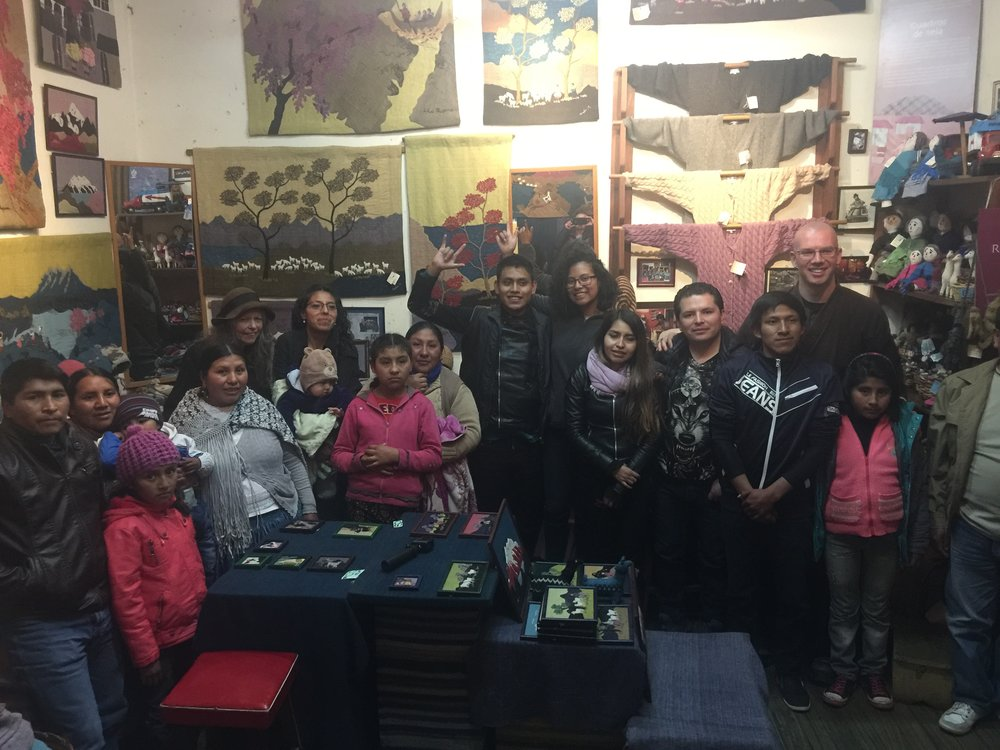Ōshin standing amongst a large crowd of Deaf Bolivians in a textiles shop.