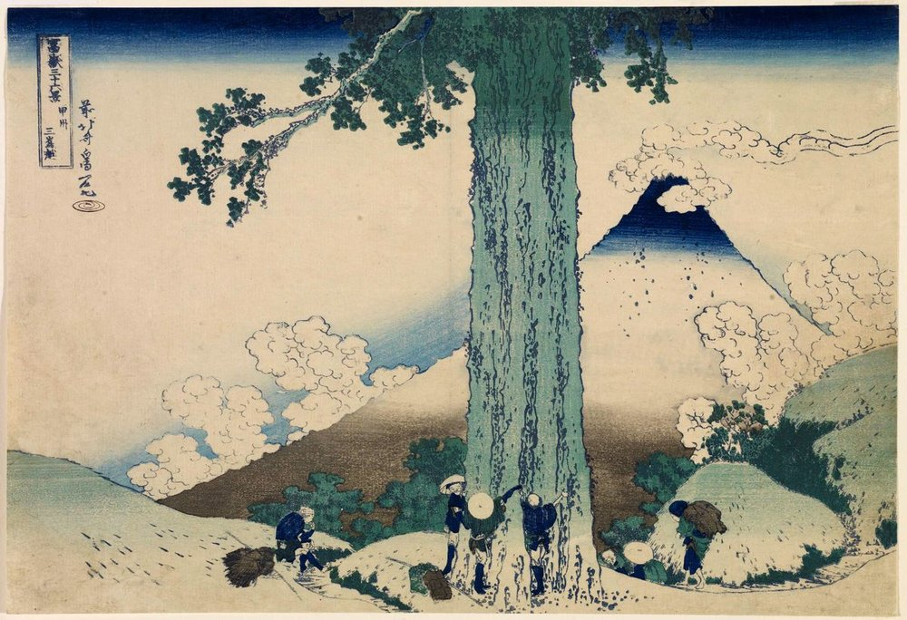 Image description: A woodblock print from Hokusai's 36 Views of Mt. Fuji, the mountain is in the background, wreathed in clouds, in the foreground men gather at the base of a large tree.