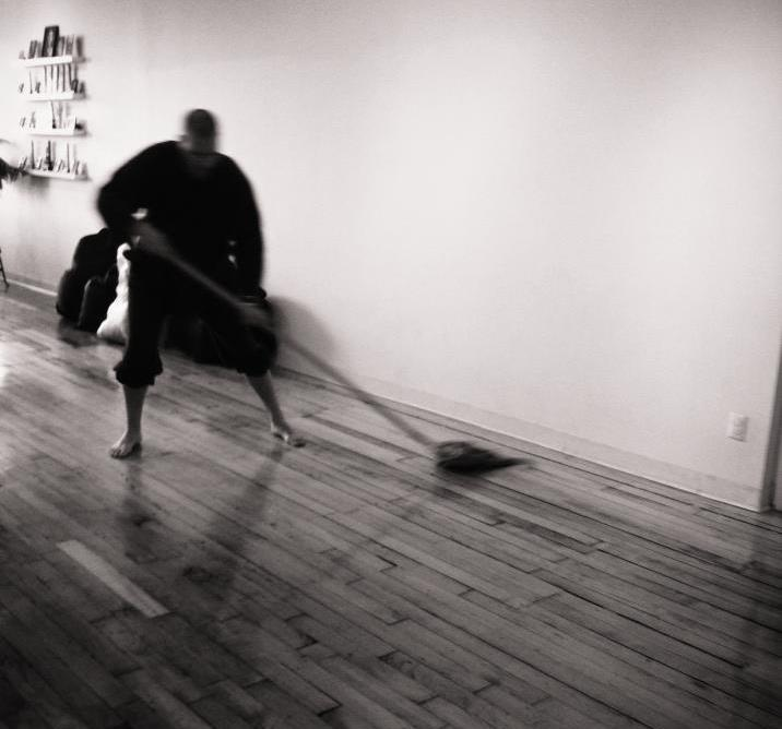 image description: a blurred black and white photo of Ōshin mopping a wooden floor.