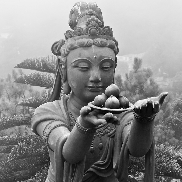 image description: a statue of a bodhisattva holding forth a plate with offerings.