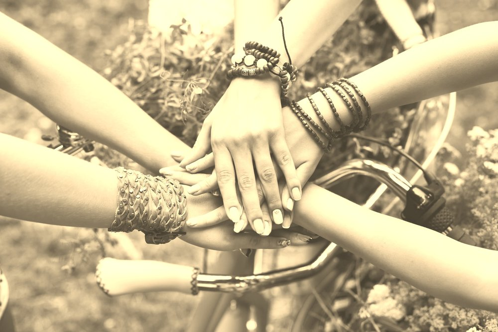 United hands of girlfriends closeup, young girls in boho bracelets