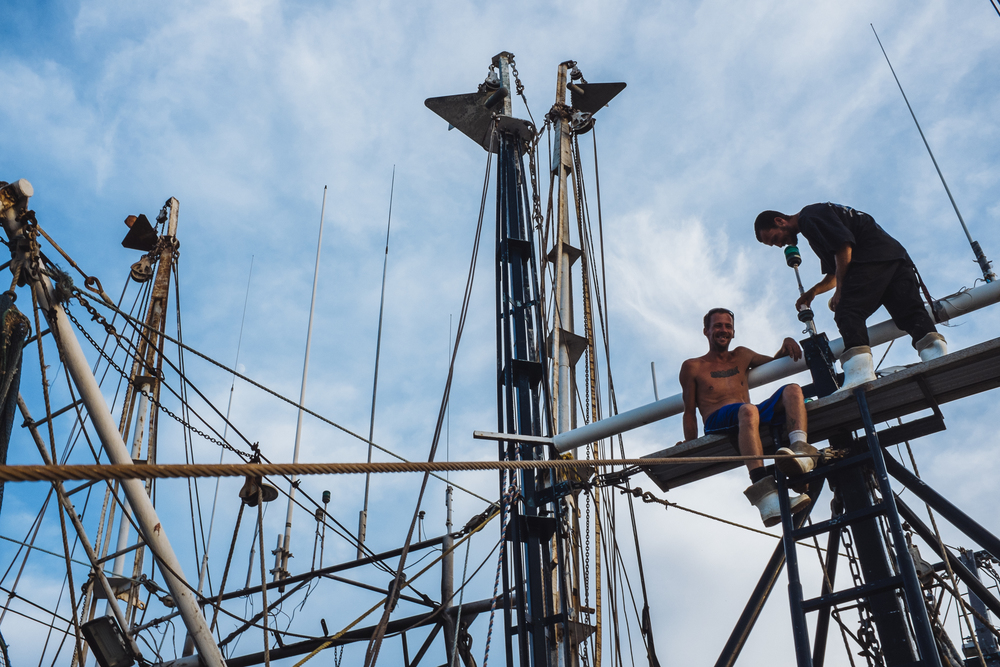 Being a shrimper at sea is mostly a balancing act. Pulling out the outriggers requires them to climb across thin beams in high seas. Here Timmy and Jessie take a break after repairing a blown bulb on the lookout.