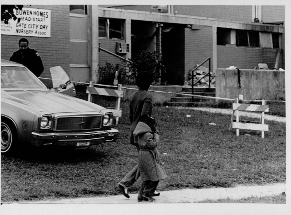 Tina and Lanecia walk past security guard at the blast site. Photograph by Steve Helber (1980) Atlanta Journal-Constitution Photographic Archives. Special Collections and Archives, Georgia State University Library.