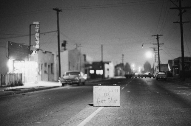 Although law and order have been re-established in the strife-torn Watts district of Los Angeles, this sign remains as a terrifying symbol of the events that passed. As a further sign of peace, Governor Edmund G. Brown ended 8/17 the curfew forbidding people from being on the streets after dark. Bettmann/CORBIS (1965)