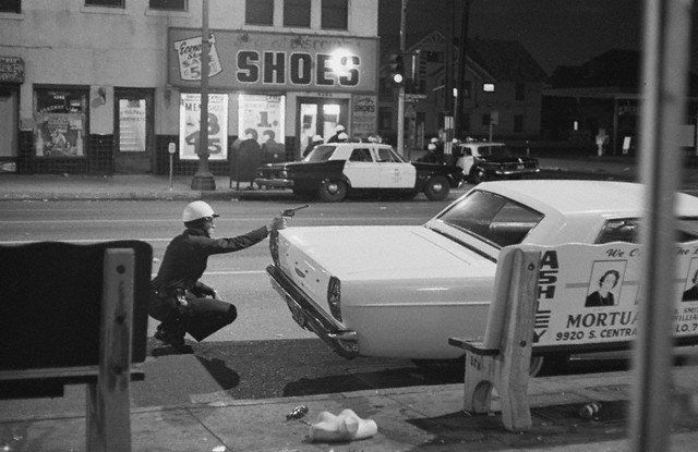 Move In On Sniper. a policeman aims his revolver at building from which a sniper was taking potshots at passing cars during rioting early Aug. 15th in the Negro community of Watts. Across the street, fellow officers crouch behind cars as they move in closer. Moments later National Guardsmen arrived on the scene and reported they had hit the sniper with return fire.  Bettmann/CORBIS (1965)
