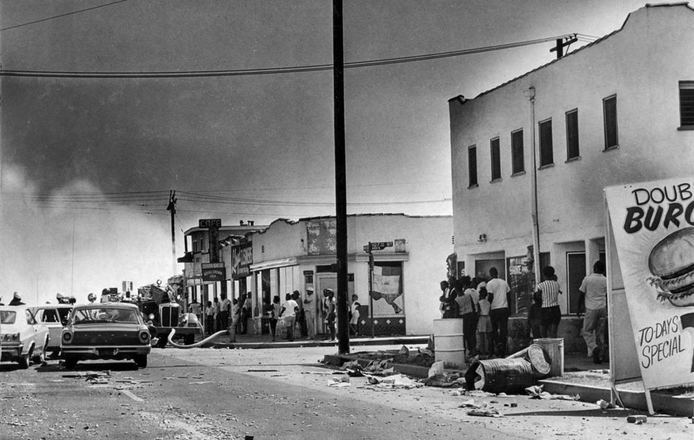 Debris litters Avalon Boulevard near 105th Street as pedestrians watch smoke rise from a building at 108th Street. (John Malmin / Los Angeles Times) 1965