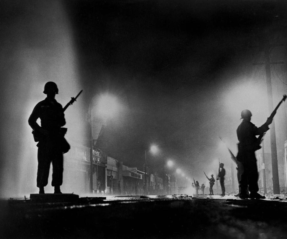 National Guard troops secure a stretch of 103rd Street, dubbed Charcoal Alley, during the Watts riots. This photo was published on the front page of the Aug. 14, 1965, edition of the Los Angeles Times. (John Malmin / Los Angeles Times)