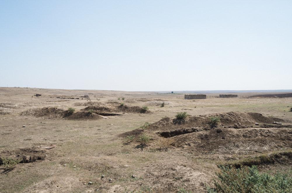 Riesige, quadratische Löcher in der Erde, die als Versteck für Geschütze und Panzer dienen. Martekert