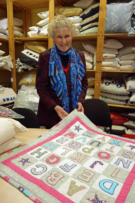 Caroline with a cot quilt made by a prisoner for Fine Cell Work