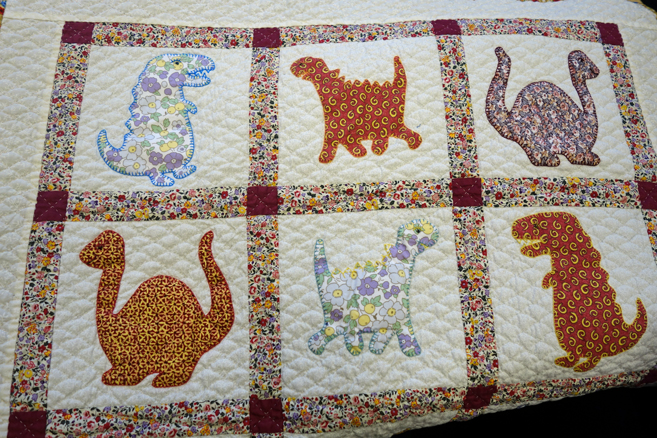 Applique Dinosaur cot quilt stitched by a prisoner for Fine Cell Work