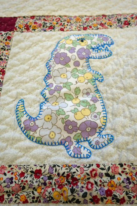 Dinosaur motif from a cot quilt stitched by a prisoner for Fine Cell Work