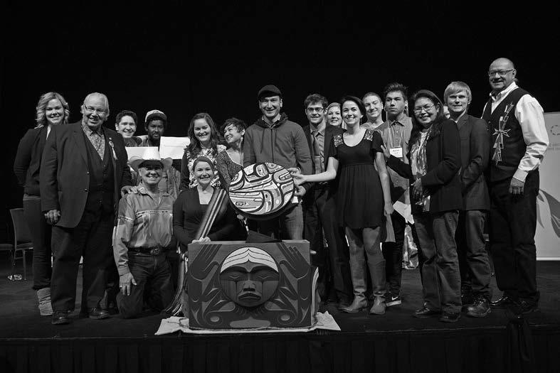 Aboriginal and non-Aboriginal representatives from 4Rs Youth Movement present the 4Rs drum made by Nisga'a artist Mike Dangeli, as an expression of reconciliation at the Truth and Reconciliation Commission Alberta National Event, March 2014. (Image from the TRC Final Report)