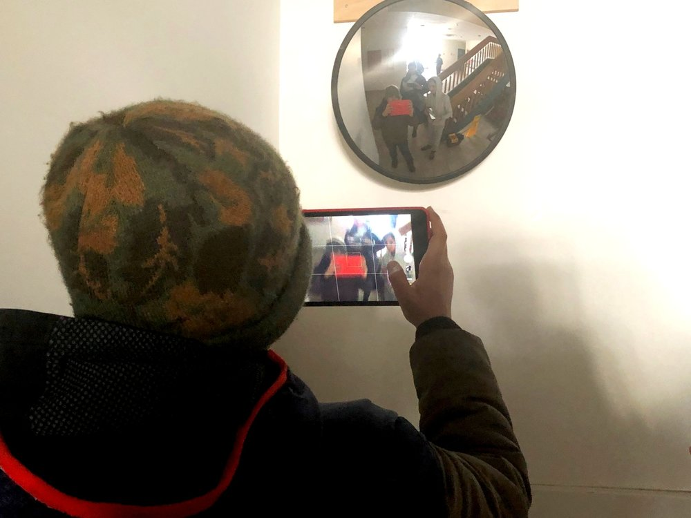 Muhammad experiments with mirrors in our photography activity.