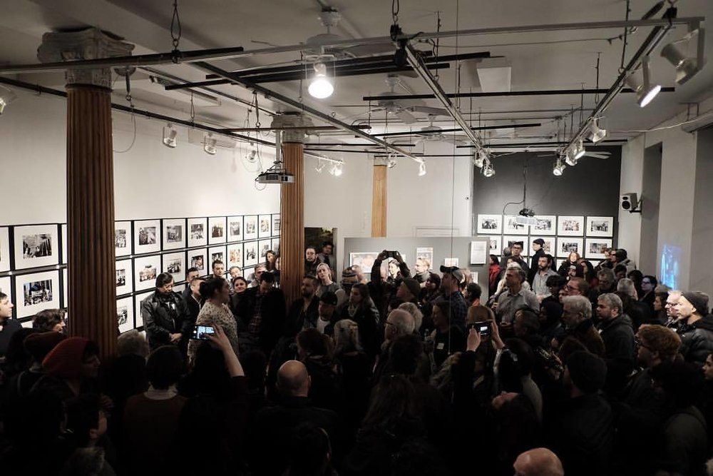 "Opening reception for "" Whose Streets? Our Streets! New York City 1980-2000 "" at the Bronx Documentary Center. Photo by Edwin J. Torres ( source )"
