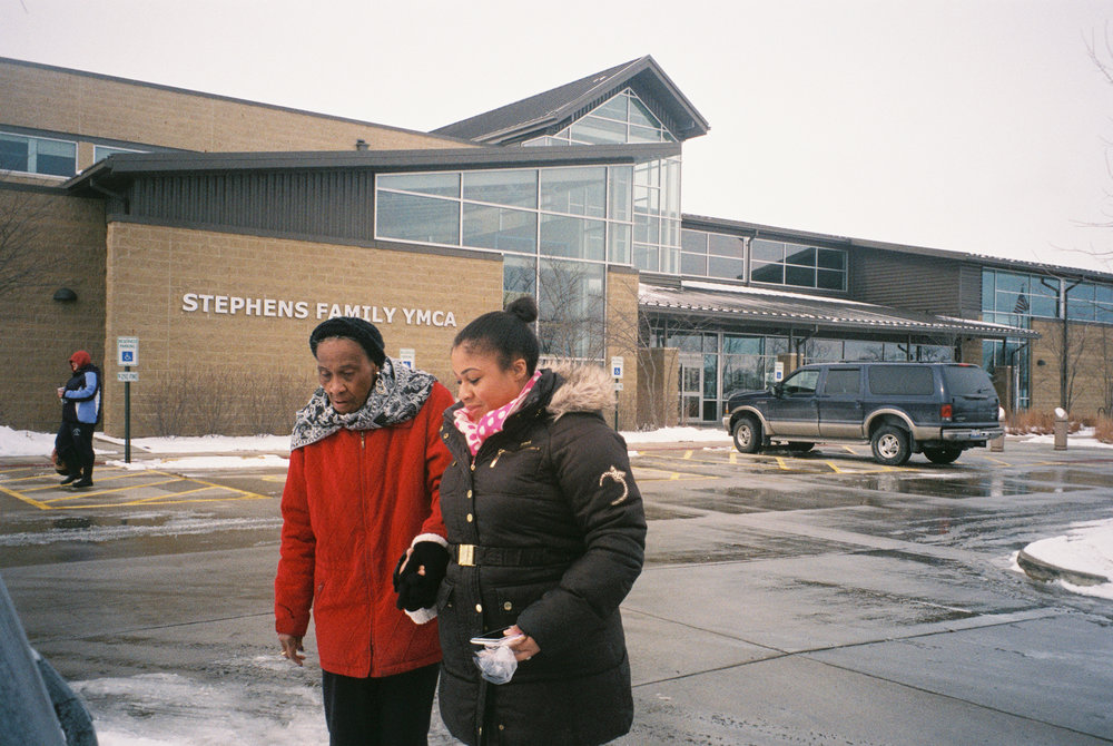 Nesa walks Shirley, 80, to the car after an exercise class at the YMCA in Champaign, Ill. Nesa works as a private home care aid during the week.